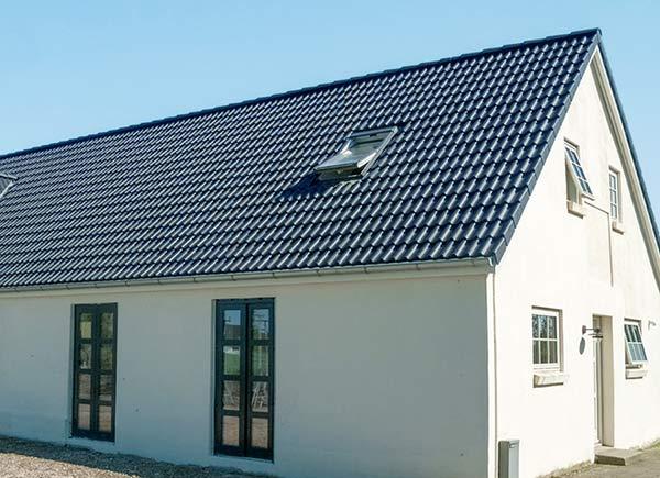 Nachher: Haus mit neuem Satteldach und Dachfenster nach Dachsanierung