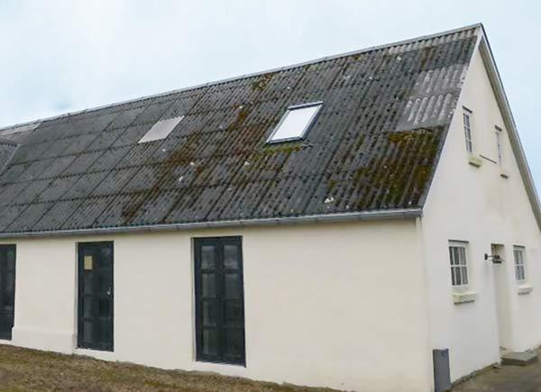 Vorher: Haus mit beschädigtem Satteldach und Dachfenster vor Dachsanierung