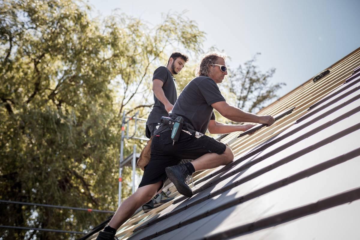 zwei Dachdecker arbeiten auf einem Satteldach