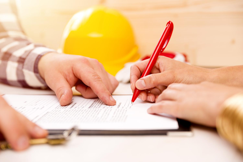 Dachdecker und Hausbesitzer unterzeichnen einen Dachdeckervertrag